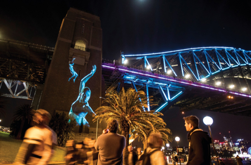 People viewing the EORA - Dark Emu light projection on the Sydney Harbour Bridge south pylon during Vivid Sydney 2018, Photo Credit: Destination NSW, Photographer: Anna Warr, 2018