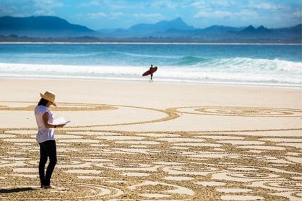 Festival Director Edwina Johnson and sand art at Wategos, Byron Bay. Image: Evan Malcolm.
