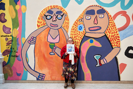 Emily Crockford alongside her work from the official launch of Studio A mural Love owls and mermaids singing in the rainbow pop, commissioned by The Art Gallery of NSW for Archie Plus, November 2021. Image by Diana Panuccio/AGNSW.